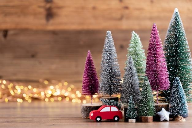 Kolorowe choinki na tle bokeh drewniane, koncepcja obchodów świąt bożego narodzenia. kartka z życzeniami.