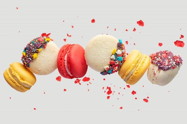 Kolorowe ciasteczka macarons. francuskie ciasta. słodkie i kolorowe francuskie makaroniki spadają lub latają w ruchu. z plasterkami