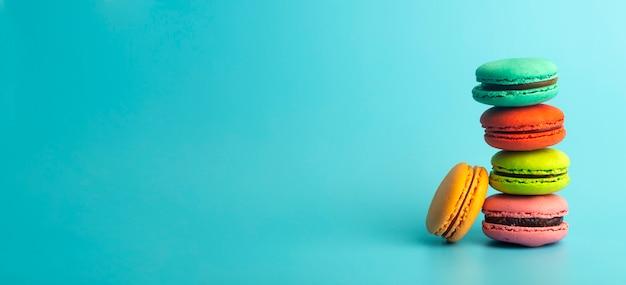 Kolorowe ciasteczka makaronik na niebieskim tle transparentu. jasne świąteczne wypieki, desery i słodycze. pieczenia w tle