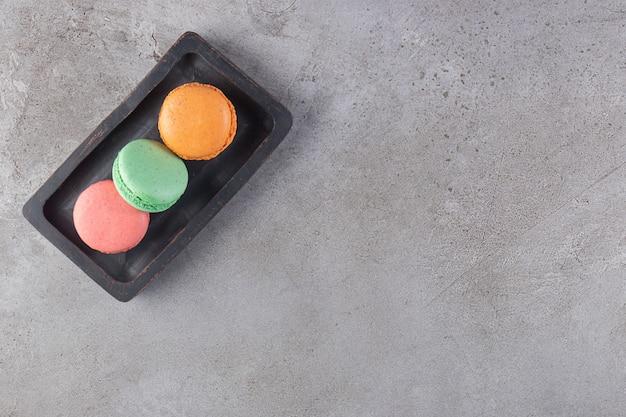 Kolorowe ciastka na drewnianym talerzu, na marmurowym stole.