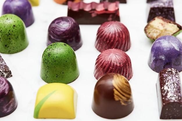 Kolorowe cukierki czekoladowe na białym tle marmuru.
