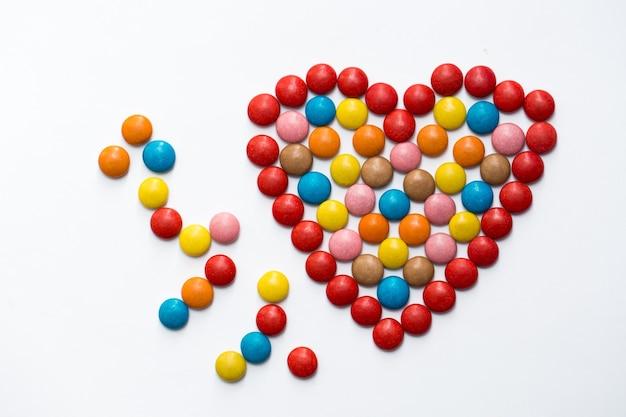 Kolorowe cukierki czekoladowe z przyciskiem m & m w kształcie miłości na białym tle.