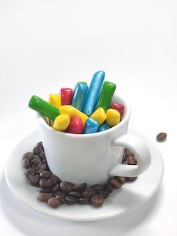 Kolorowe cukierki do żucia w kubku na białej ścianie