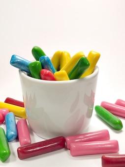 Kolorowe cukierki do żucia w kubku na białym tle