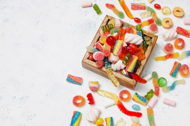 Kolorowe cukierki, galaretka, pianka na lekkiej powierzchni. widok z góry z miejsca kopiowania