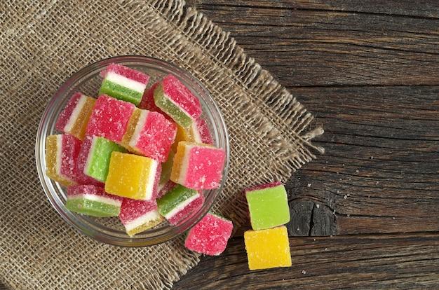 Kolorowe cukierki galaretki w szklanej misce na ciemnym tle drewnianych, widok z góry