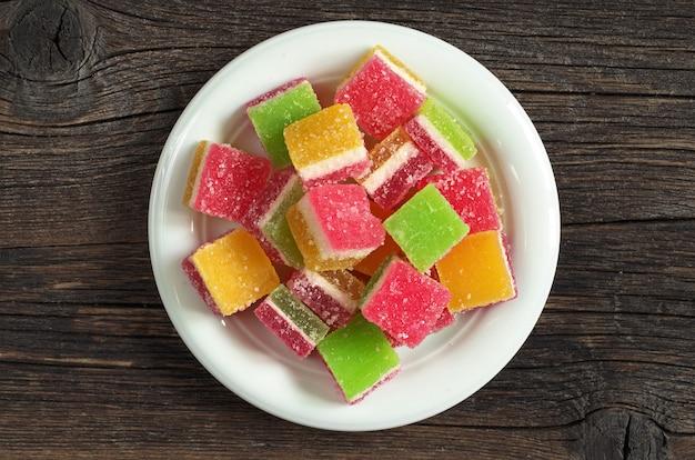 Kolorowe cukierki galaretki w talerzu na ciemnym tle drewnianych, widok z góry