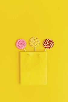 Kolorowe cukierki lollypop cukierki karmelowe na patyku w żółtym opakowaniu papierowym