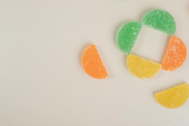 Kolorowe cukierki marmoladowe na beżowej powierzchni