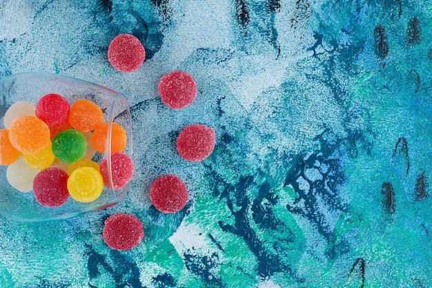 Kolorowe cukierki marmoladowe w szklance, na niebieskim tle.