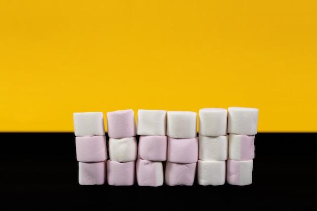 Kolorowe cukierki marshmallow na żółtym i czarnym tle. zbliżenie