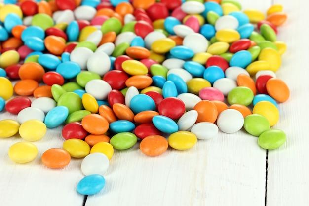 Kolorowe cukierki na białym tle drewnianych