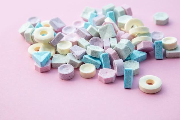 Kolorowe cukierki na białym tle na różowym tle. naturalne światło, widok z góry