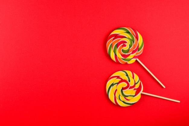 Kolorowe cukierki na czerwonym tle. lizak. widok z góry. skopiuj miejsce.