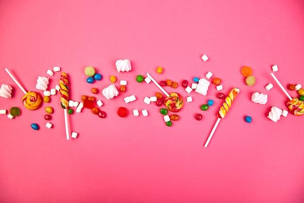 Kolorowe cukierki na różowo. leżał płasko