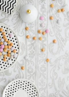 Kolorowe cukierki na talerzach polkadot na obrusie kwiatowym