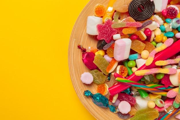Kolorowe cukierki na żółtym