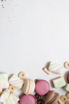 Kolorowe cukierki rozrzucone na białym tle. makaroniki, zefiry i wybór płatków śniadaniowych