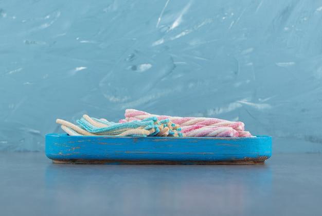 Kolorowe cukierki skręcone na niebieskim talerzu.