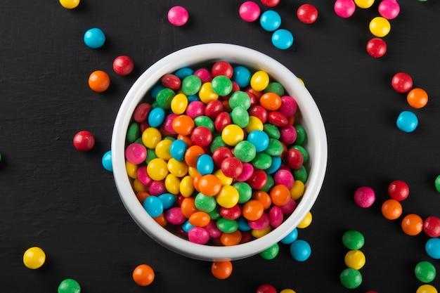 Kolorowe cukierki. tło kolorowe słodycze. czarne tło.