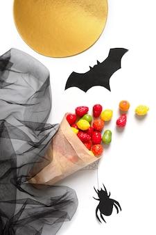 Kolorowe cukierki w papierowej torbie na białym tle widok pionowy