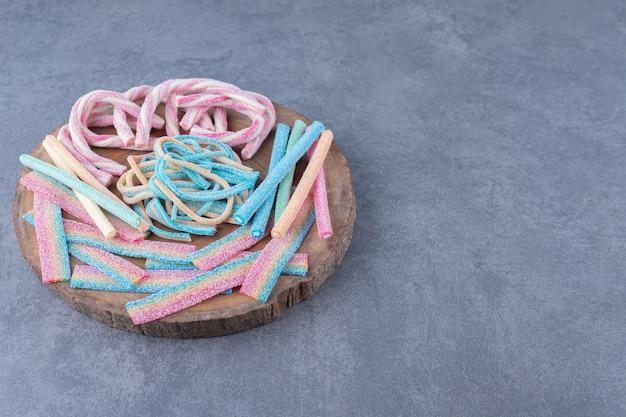 Kolorowe cukierki w postaci skręconej liny na desce na marmurowym stole.