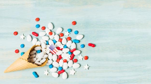 Kolorowe cukierki z usa flaga w gofra rożku na błękitnym textured tle