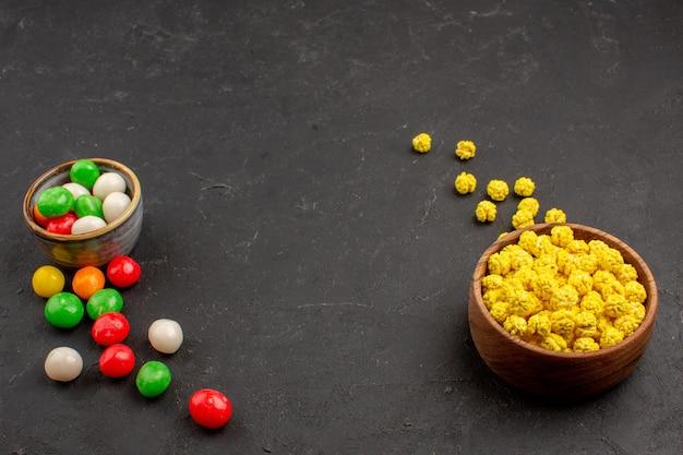 Kolorowe cukierki z widokiem z przodu na ciemnej przestrzeni