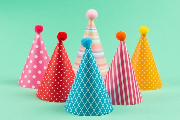 Kolorowe czapki urodzinowe na miętowej ścianie.
