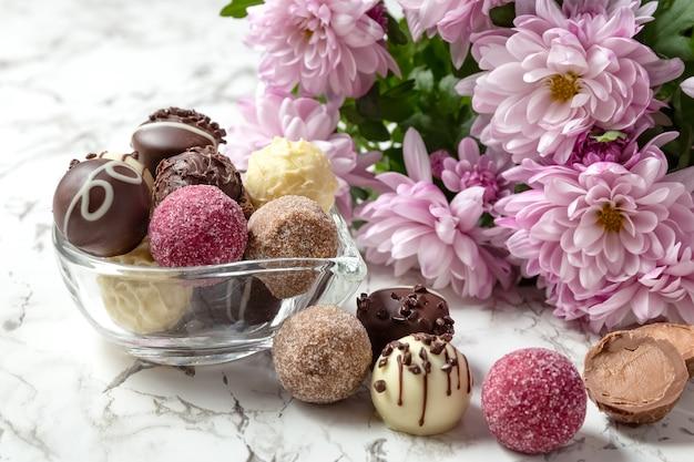 Kolorowe czekoladki na szklanej misce z różowymi kwiatami na stole z białego marmuru.