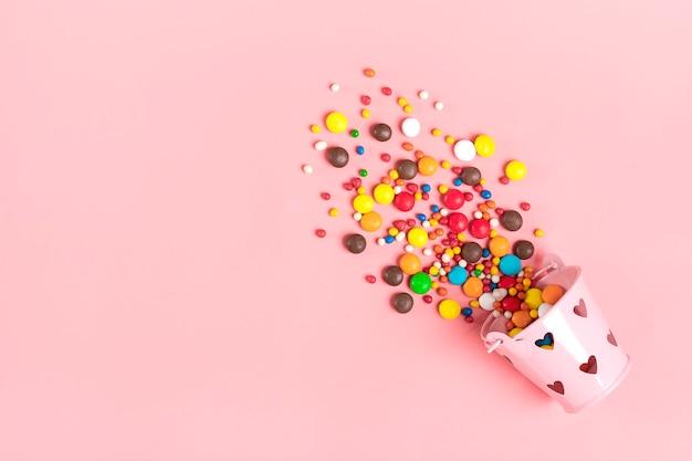 Kolorowe czekoladowe słodycze wysypały się z wiadra z sercami na różowym leżaku flat