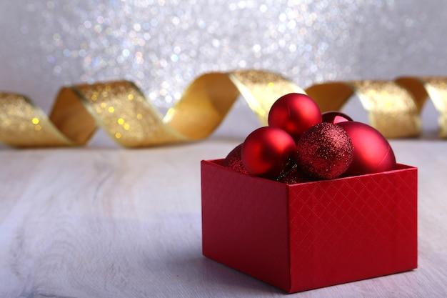 Kolorowe czerwone prezenty z bombkami na srebrnym tle