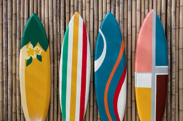 Kolorowe deski surfingowe stojące na bambusowej drewnianej ścianie