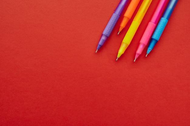 Kolorowe długopisy z bliska czapki, czerwone tło. artykuły biurowe, akcesoria szkolne lub edukacyjne, narzędzia do pisania i rysowania