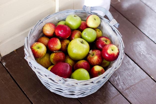 Kolorowe dojrzałe jabłka w białym koszu