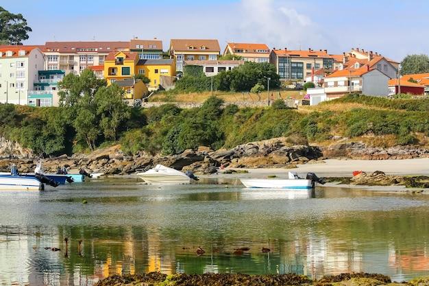 Kolorowe domki na szczycie klifu nad morzem i małe łódki na wodzie.