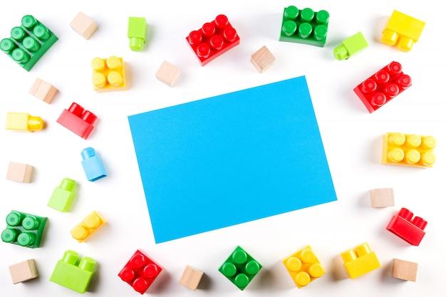 Kolorowe drewniane kostki i plastikowe klocki z niebieską pustą kartą papieru na białym tle