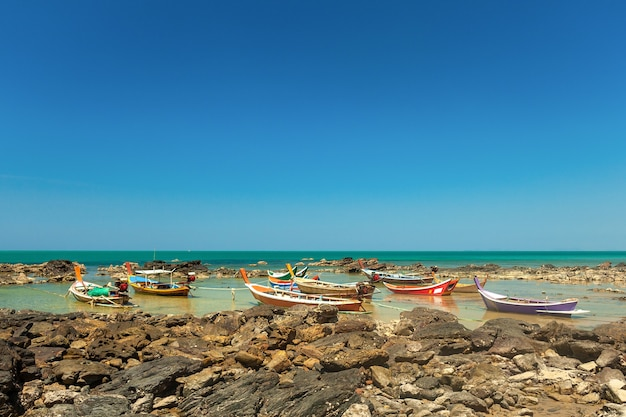 Kolorowe drewniane łodzie rybackie w stylu tajskim stoją przy skalistym brzegu na tle morza i błękitnego nieba.