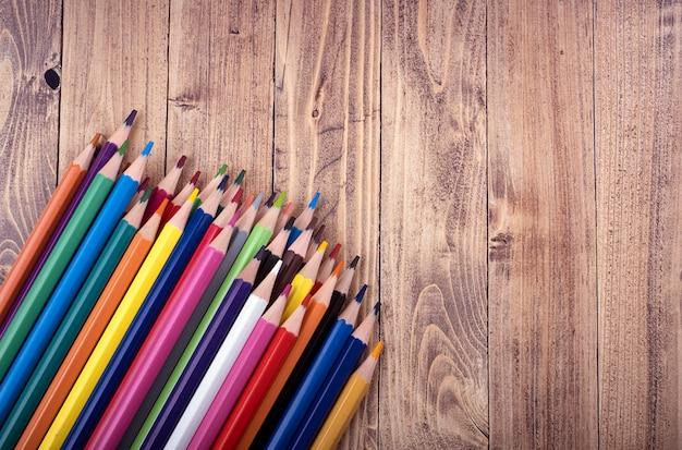 Kolorowe drewniane ołówki na drewnianej podstawie.