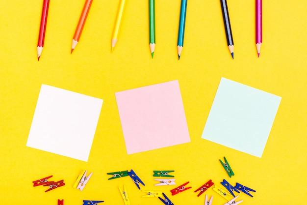 Kolorowe drewniane ołówki, szpilki i kartki do pisania na żółtym tle