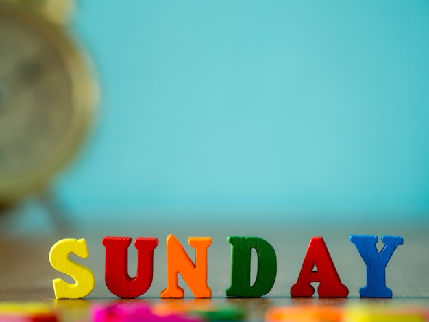 Kolorowe drewniane słowo niedziela na drewnianym stole i vintage budzik