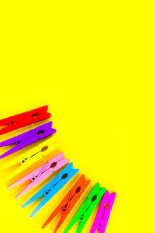 Kolorowe drewniane spinacze do bielizny na żółtym tle. zamknij się, skopiuj miejsce. minimalizm, oryginalne i kreatywne zdjęcie. bądź innym.