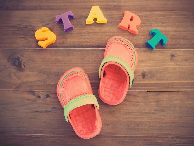 Kolorowe dziecięce sandały gumowe i kolorowe alfabety uruchamiaj słowo na drewnianej podłodze