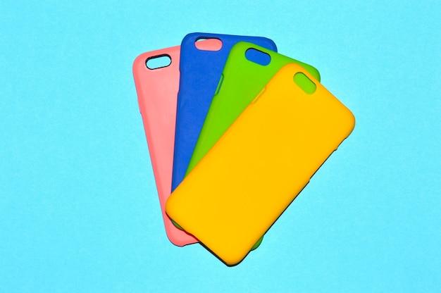 Kolorowe etui na telefony na niebieskim tle
