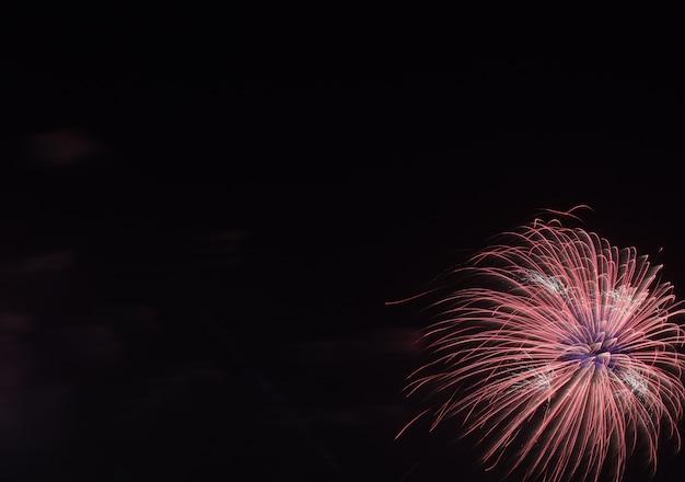 Kolorowe fajerwerki na czarnym tle nieba nad wodą