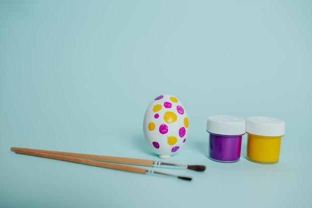 Kolorowe farby i pędzle. proces malowania pisanek. kropkowane jajko wielkanocne.