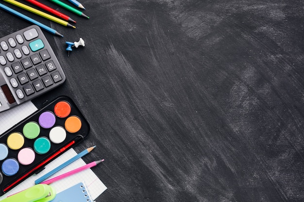 Kolorowe farby, kalkulator i ołówki na szarym tle