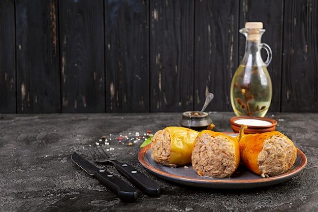 Kolorowe faszerowane papryki z ryżem i mięsem mielonym na drewnianym stole.