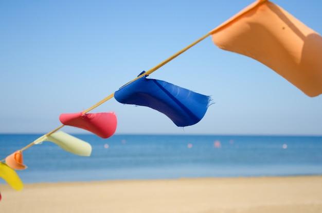 Kolorowe flagi trznadel na piaszczystej plaży nad morzem w słoneczny dzień.
