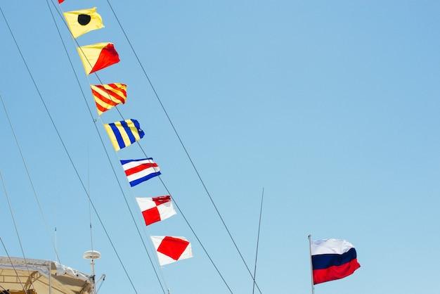 Kolorowe flagi żeglarskie pływające na wietrze z linii masztu żaglówki podświetlanej w błękitne niebo przez słońce.